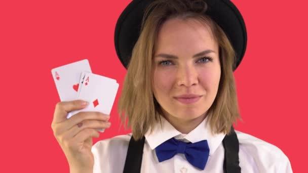 Croupiermädchen in weißem Hemd und Hut zeigt Karten und lächelt. Vier Leichen. Roter Hintergrund