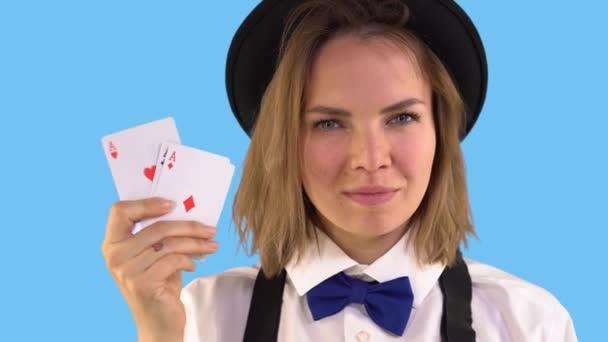 Croupiermädchen in weißem Hemd, Hut und Fliege zeigt Spielkarten und lächelt. Vier Asse. Blauer Hintergrund