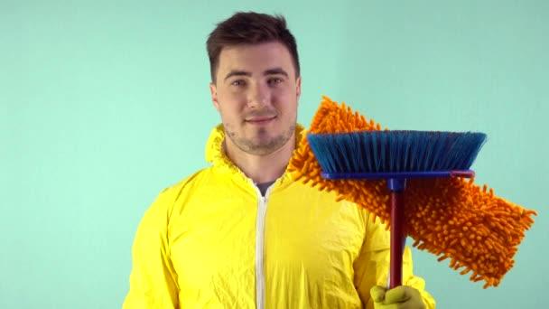 Čistič ve žlutém obleku a žlutých rukavicích drží v jedné ruce mop a ve druhé nádobu s tekutinou na modrém pozadí, muž souhlasně potřásá hlavou.