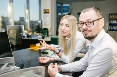 A businessman who is discussing a job with his female co-worker By consulting about the work in the office. Copy space.
