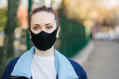 Closeup pretty woman wearing a face mask to protect against pollution or disease.COVID-19 Pandemic Coronavirus Young girl in city street wearing face protective mask.Copy space.Quarantine.Stay at home