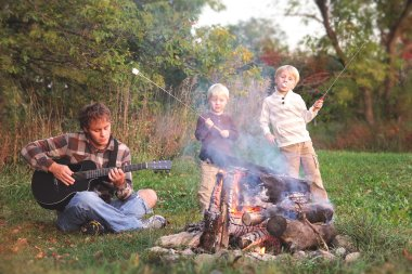 Father and Sons Roasting Marshmallows and Playing Guitar by Camp