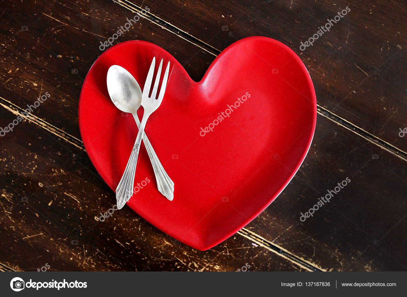 An empty red heart shaped dinner plate with a silver spoon and fork is sitting on an old worn out wood planked table. u2014 Photo by Christin_Lola & Heart Shaped Dinner Plate with Fork and Spoon on Worn Wood Table ...