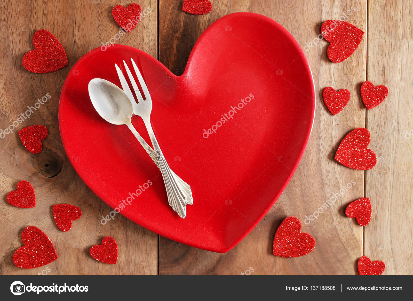 A red heart shaped dinner plate with fine German silver fork and spoon is on a rustic cherry wood planked table surrounded by Valentineu0027s Day confetti. & Heart Shaped Dinner Plate with Fine Silverware on Wood Plank Tab ...