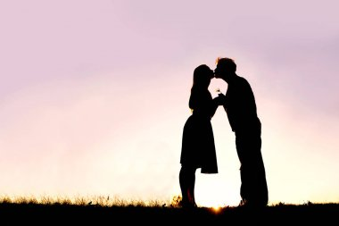Silhouette of Loving Young Couple Kissing Outside on Date at Sun