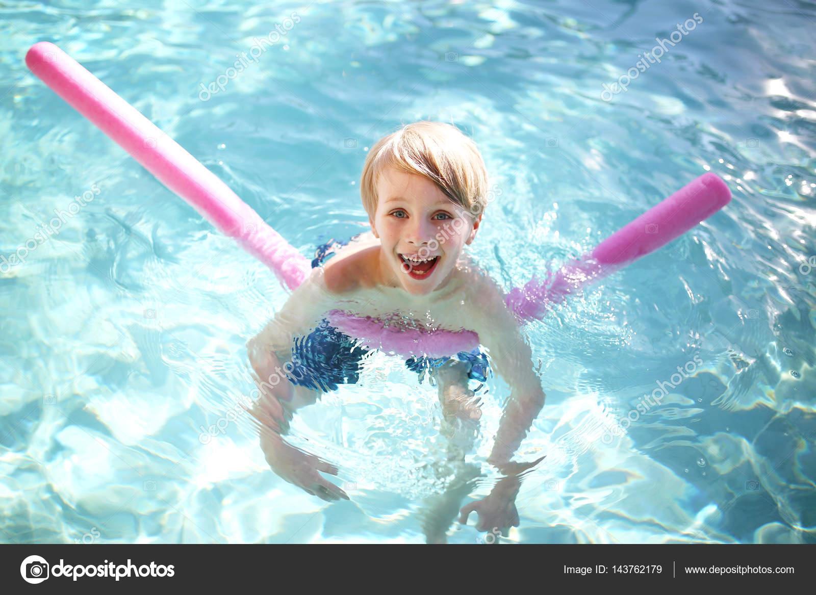 7477d8dcf Un niño de 7 años de edad, feliz y joven muchacho sonríe mientras toma  clases de natación con una diversión flotante fideos fuera en la piscina en  un día de ...