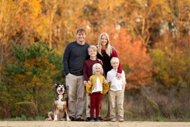 Happy Young Family of Parents and Children and Pet Dog Outside o