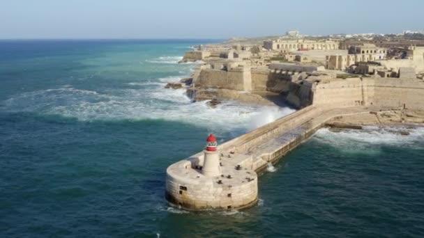 Letecký pohled na červený maják, pevnost Ricasoli. Velké vlny ve Středozemním moři. Grand Harbor. Malta country