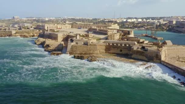 Letecký pohled na červený maják a pevnost Ricasoli. Velké vlny. Malta Island