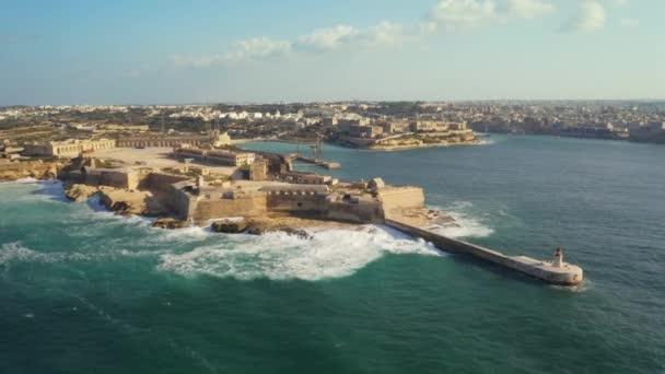 Letecký pohled na červený maják a pevnost Ricasoli. Velké vlny. Malta country