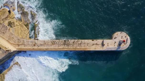 Vzdušný výhled na červený maják, velké bouřkové vlny, Středozemní moře. Fort Ricasoli, Grand Harbor. Kamera jede nahoru. Malta Island