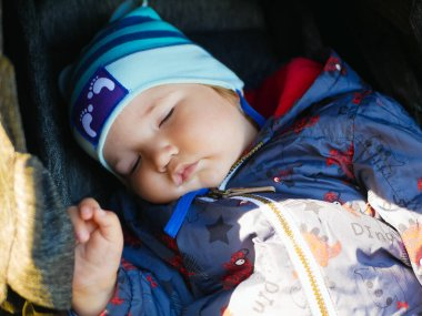 sleeping baby in a stroller for a walk. close-up. Cute little boy sleeping outdoors