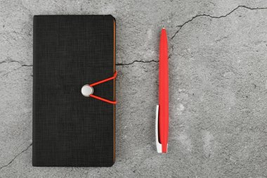 black notebook and red pen. Blank notebook and red pen. Blank notebook and red pen on gray concrete background. view from above.