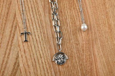 silver jewelry around the neck. Silver chains. Handmade. against the general background