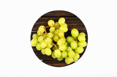Green grapes on a round wooden plate. White background. view from above. A place to write. Juicy bunch of grapes on a wooden background.