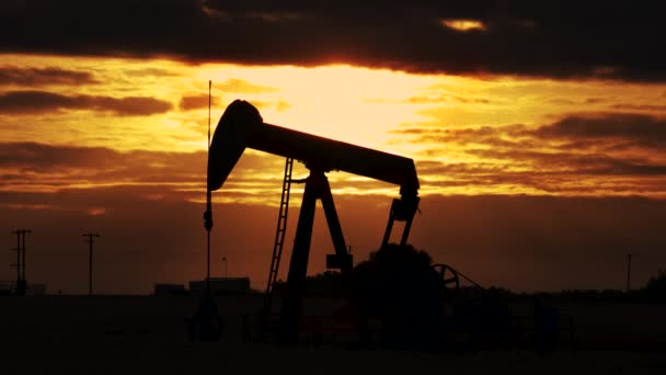 Tökfej. Olajkút.Sziluett egy olajszivattyú jack a fúrótorony, ahogy a nap lemegy a háttérben. Egy olajpumpa emelő a búzamező közepén, gyönyörű naplemente égbolttal..