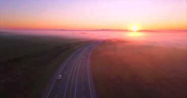 Aerial view of road with cars, fields covered with fog at sunrise. Russia