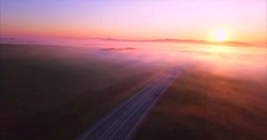 Flying sideways above road, fields covered with fog, rising sun. Russia