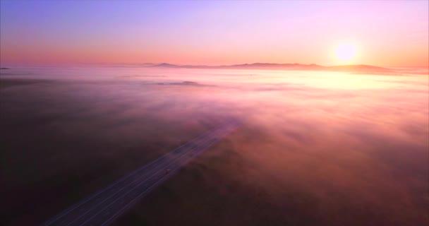 Sestupně nad silnicí s automobily, pokryté pole mlhy za svítání. Rusko