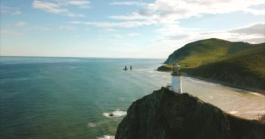Slowly flying near rocky cliff with lighthouse. Seashore is on background.Russia