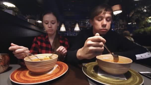 Mladý atraktivní pár na večeři v kavárně, jíst tom yum polévka, mluví