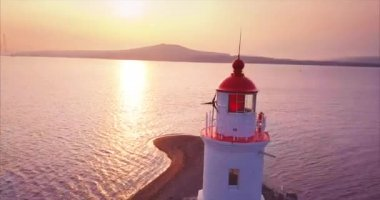 Flying around, aerial panoramic view old lighthouse at amazing sunrise