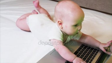 Portrait of adorable 6 months baby boy lying in bed and playing with laptop