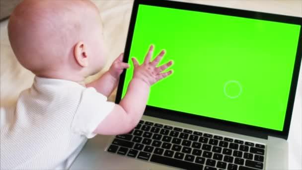 6 hónapos baba fiú az ágyon előtt laptop chroma-kulcs képernyő