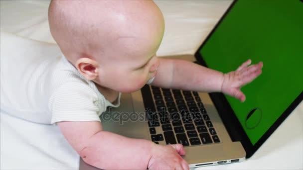 6 měsíců starý chlapeček leží na posteli před notebookem s chroma klíč obrazovky