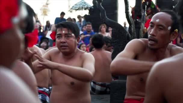 BALI, INDONESIA - JULY 10, 2019: shirtless indonesian men with red flowers behind ears moving and singing while performing traditional Kecak dance