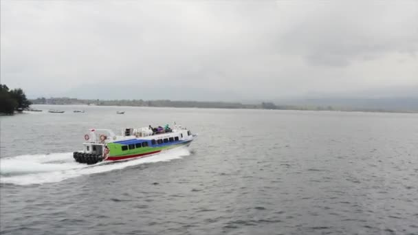 GILI AIR, INDONESIA - JULY 4, 2019: Aerial panoramic view of green ferryboat with tourists sailing fast on ocean waves with amazing island with mountains on background