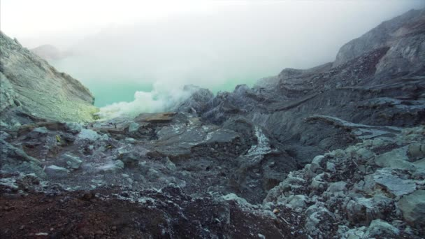 time lapse of tourists walking along crater while exploring Ijen volcano caldera with acid fumes coming from it. East Java, Indonesia