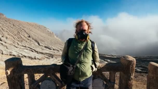 Zooming in timelapse portrait of man in respirator with caldera and acid fumes , Ijen volcano, East Java, Indonesia