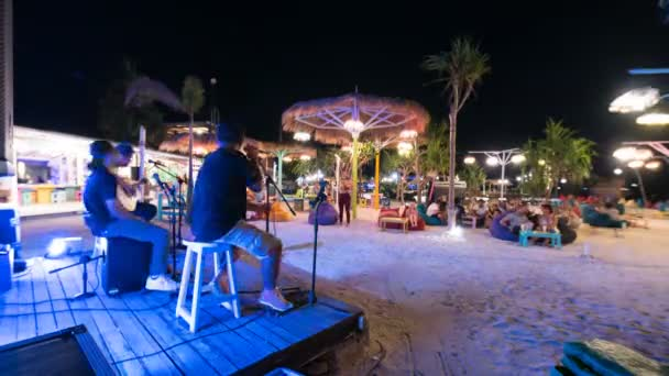 GILI AIR, INDONESIA - JULY 2, 2019: Timelapse of performance of musical band on wooden stage at night resort beach full of tourists