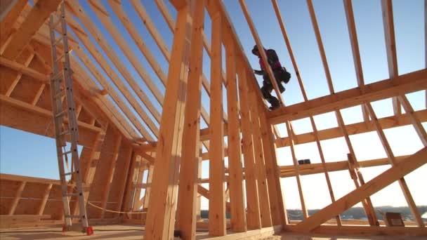 stavitelé pracující v nedokončeném rámu domu interiér s dřevěnými trámy střechy a stěny s modrou oblohou na pozadí