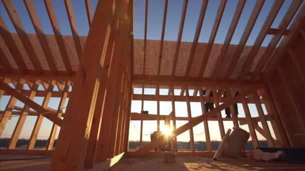 pohled na stavitele kryjící střechu s vodotěsnou vrstvou v nedokončeném rámu interiér domu s dřevěnými trámy střechy a stěn s modrou oblohou na pozadí