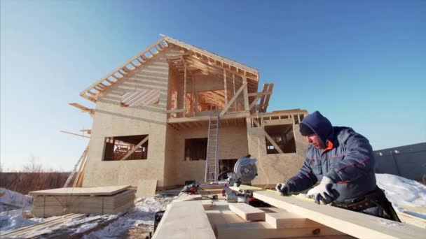Builder measuring wooden plank with measuring tape to cut with circular saw while standing near frame house under construction on background