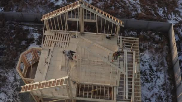 Top aerial ascending view of of builders lifting attic frame on place. concept of frame house under construction
