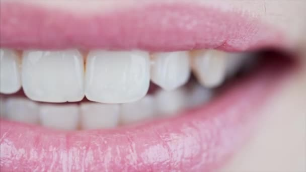 Macro view of female mouth with light pink lipstick on lips and beautiful white teeth speaking