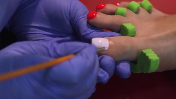 Frau macht Maniküre der Fußnägel in einem Schönheitssalon mit Nahaufnahme weißen Nagellack mit Applikator auftragen. Der Meister lackierte seine Nägel mit Lack. Details zum Nagellack