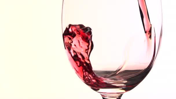 Nalévání červeného vína do skla na bílém pozadí
