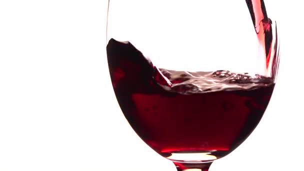 Red wine poured into glass on white background