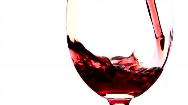 Rotwein in Glas auf weißem Hintergrund gegossen