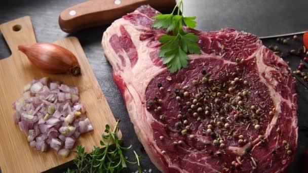 Ein rohes Fleisch mit Gewürzen und Pfeffer bestreuen