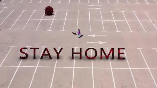 Dáma se psem chůze na prázdném parkovišti s názvem Stay Home a koronavirovou infekcí šíření (covid-19) - Koncept