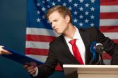 nespokojený muž držící schránku na tribuně na pozadí americké vlajky