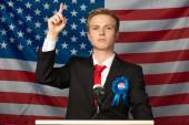 Selbstbewusster Mann mit erhobener Hand auf der Tribüne vor amerikanischem Flaggenhintergrund