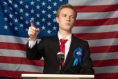 Emotionaler Mann zeigt mit Finger auf Tribüne vor amerikanischem Flaggenhintergrund