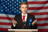 Fotografie Emotionaler Mann auf der Tribüne während einer Rede vor dem Hintergrund der amerikanischen Flagge