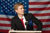 Selbstbewusster Mann auf der Tribüne vor dem Hintergrund der amerikanischen Flagge